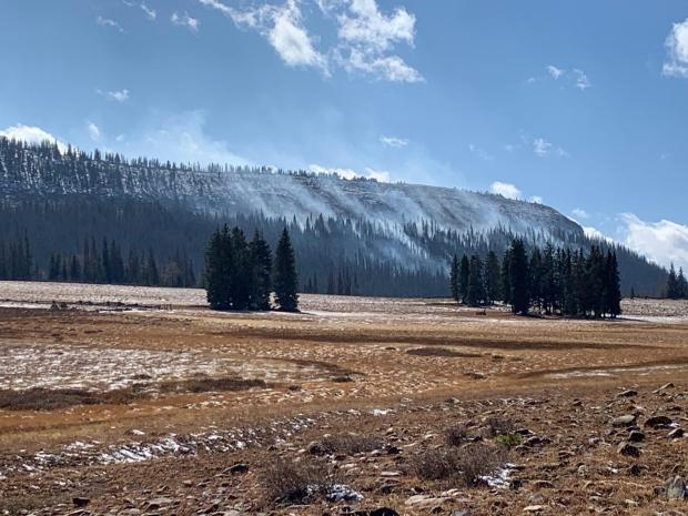 A barbwire fence is in the foreground, with snow mostly covering a grassy field. Smoke rises on a mountain in the background.