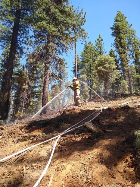Photo of firefighter spraying water on a hot spot in the fire perimeter