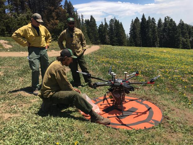A unmanned aircraft system patrols the fire perimeter for hot spots.