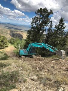 A turqouise excavator reaches as it completes work on the Bear Fire.
