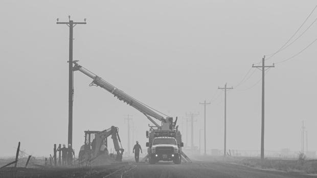 Work crews work on restoring power lines in a haze caused by wildfires along the Pacific Coast.