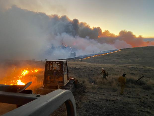A smoky fire consumes farmland as two bulldozers form a fire break.