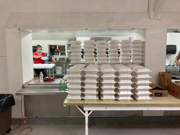 Stacks of boxed meals sit on top of a counter waiting for fire crews to retrieve them.