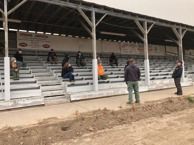 A group of 12 Logistics Section staff sit at least 6 feet apart during a meet in the bleachers of the fairgrounds during the Whitney Fire.