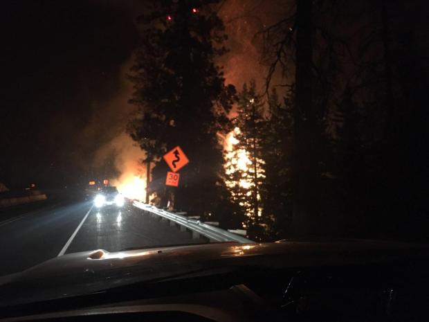 A nighttime view of the fire with trees burning in the background behind a vehicle parked on Hwy 12.