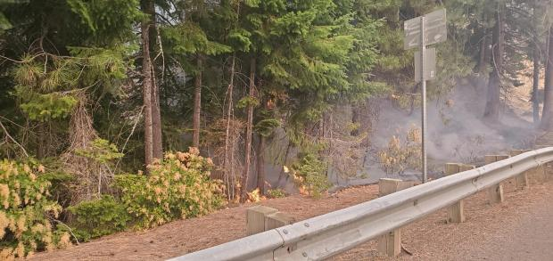 Flames creep along the ground behind a highway guardrail on Highway 12 on September 16, 2020.