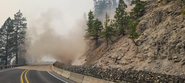 Dust rises into the air as a small landslide roles down a hillside adjacent to Hwy 12 in the Cold Creek Fire area on 9-16-2020.