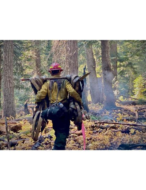Firefighter carrying used hose